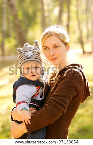 Baby with mother outdoors close to nature and have fun