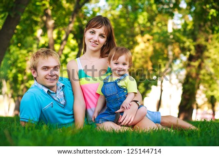 baby with parents in a green summer park
