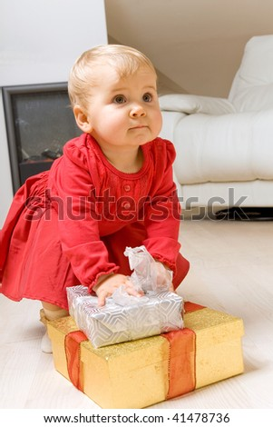 Baby with presents in living room