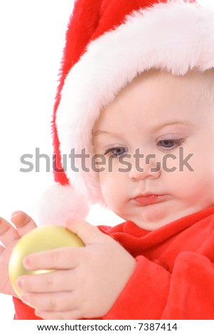 baby with santa hat holding ornament