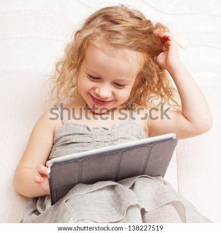 Baby with tablet computer. Little child playing at home on sofa