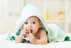 baby with teether in mouth under bathing towel at nursery