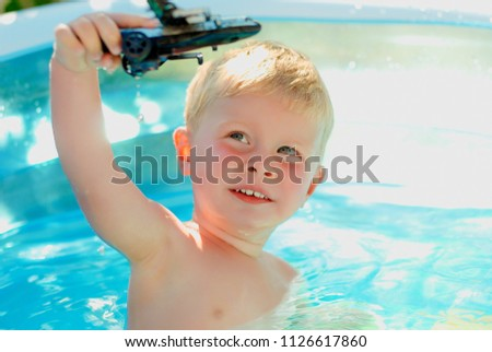 a903c6a884 Baby with toy plane in swimming pool. Little boy learning to swim in outdoor  pool