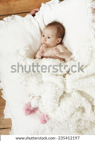 baby with white blanket, lying on a pillow
