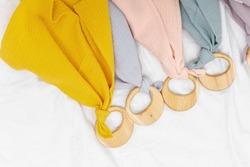 Baby wooden teething toys with multi-colored fabrics on white background