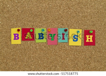 Babyish word written on colorful sticky notes pinned on cork board.
