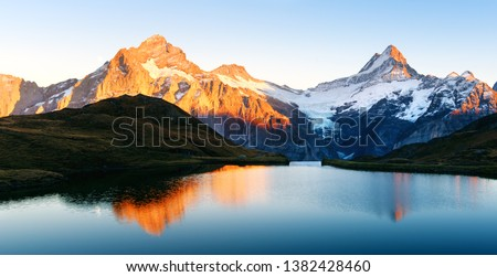 Bachalpsee lake with reflection in Swiss Alps mountains. Glowing snowy peaks on background. Grindelwald valley, Switzerland. Landscape photography #1382428460