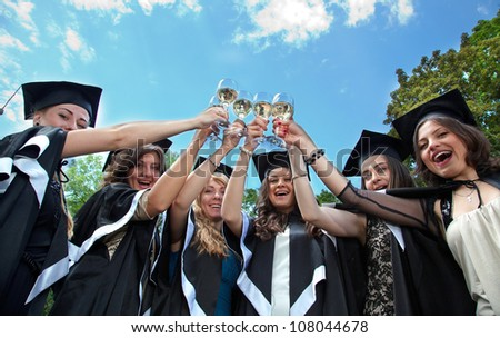 Bachelor graduates celebrate with a glass of white wine in mantles