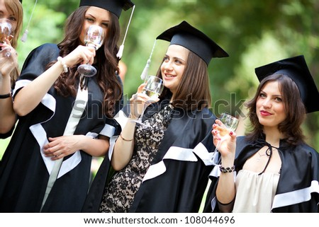 Bachelor graduates celebrate with a glass of white wine in mantles - stock photo