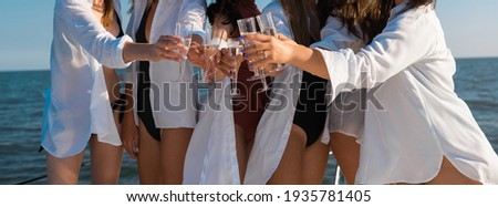 bachelorette party on a yacht on the high seas. a group of bridesmaids and a bride dressed in swimwear and white shirts drinking champagne from glass glasses on a sunny day. Foto stock ©