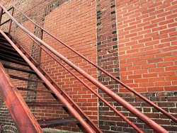back alley steps stairs rusting against a retro weathered aging brick warehouse building