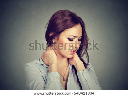 Back and spine disease. Closeup portrait tired woman massaging her painful neck isolated on gray wall background. Human face expression. Chronic fatigue
