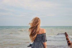 back beautiful slim girl with long flowing blond hair in the wind against the background of the sea and horizon. concept expectations, light sadness