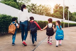 Back family parent happy children kid boy son kindergarten holding hand carry school backpack walking sidewalk to school. Young mom smile have funny, Back to school first day of semester concept