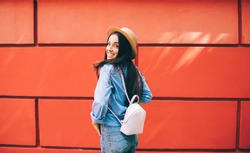 Back half length portrait of cheerful hipster girl in trendy apparel rejoicing at urban setting feeling excited from travel lifestyle, happy woman in stylish hat enjoying good mood near copy space