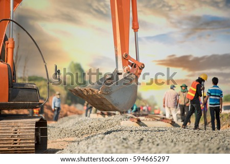 Back hoe and blurred construction worker in safety uniform in railway construction,construction site background