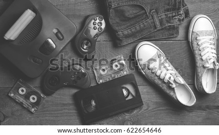 Back in the 90s. Shoes, audio tapes, video tapes, game console, jeans. Top view. Flat lat. Foto stock ©