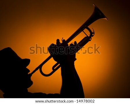 back light musician playing trumpet on orange background