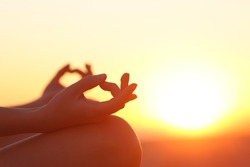 Back light of a woman hands exercising yoga at sunset with a warmth background