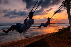 Back light portrait of a couple silhouette sitting on swing watching a sunset on the beach with the sun in a warmth background. Man and woman playing swing against sunny sunset on Sri Lanka