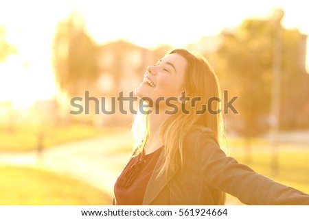 Back light portrait of a happy single teen girl breathing fresh air at sunset in a park with a warm yellow light and urban background
