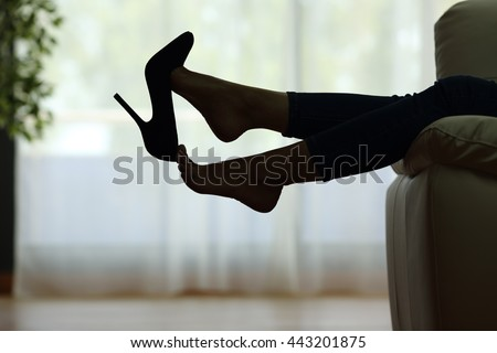Back light silhouette of a woman resting with feet taking off shoes on a couch at home with a window in the background