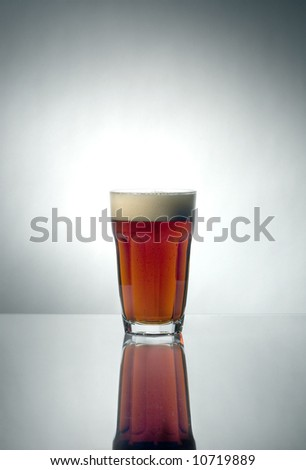 Back-lit glass of home-made beer on reflective surface