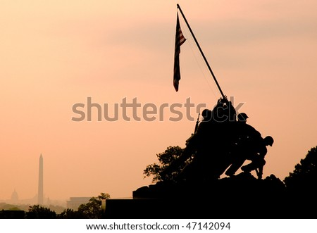 back lit Marine Corps War Memorial Iwo Jima statue and American Flag at sunrise - stock photo
