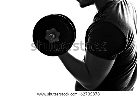Back lit silhouette of a young man lifting weights in black and white.