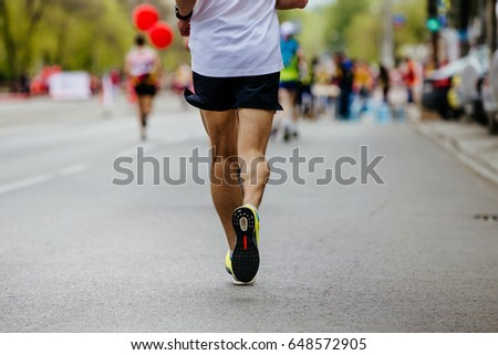 back male runner running streets of the city on background of runners #648572905