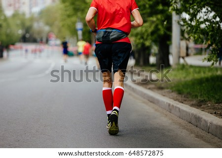 back man runner in red compression socks running street of the city #648572875
