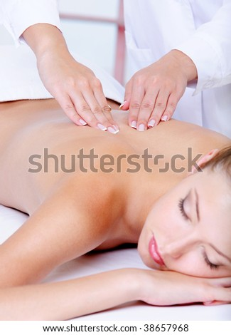 Back massage for the young pretty woman - close-up portrait - stock photo