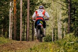 back motocross enduro racer riding on forest trail