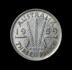 Back of a 1959 Australian three pence Silver coin on a black background