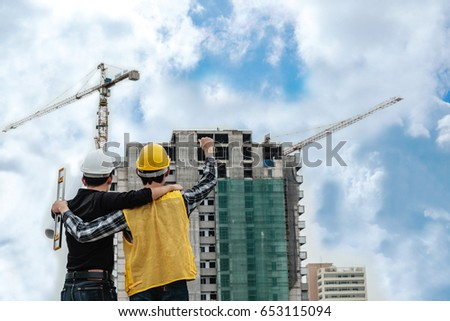 back of a building builder Hug each other and raise arms with delight for success.
