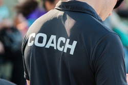 back of a coach's black shirt with the white word Coach written on it