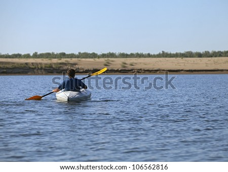 Back of a man rowing in the canoe