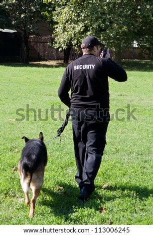 back of a security guard with a dog - stock photo