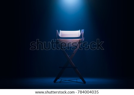Back of a vintage director chair on a smokey background / high contrast image #784004035