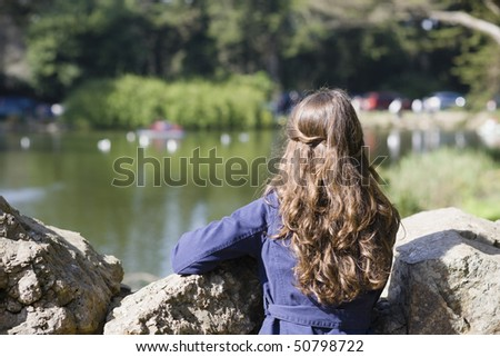 Back of a  Woman With Long Brown Hair Looking Over Rocks at a Pond