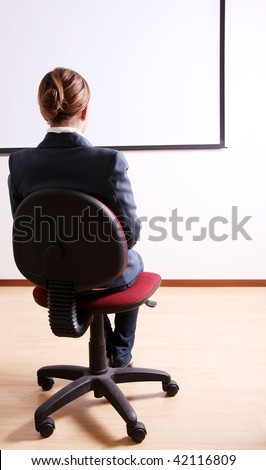Back of a young woman in an office chair