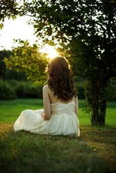 Back of a young woman with curly long hair sitting on the green grass in the park at summertime, admiring the sunset.