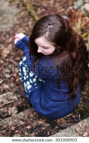 Back of a young woman with long brown wavy hair sitting on a step waiting