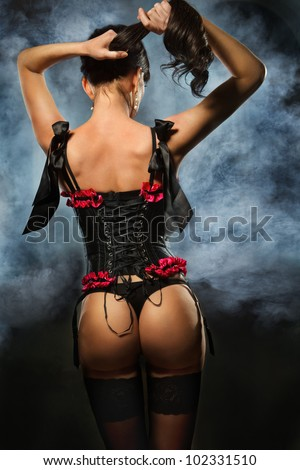 Back of alluring brunette dressed up in black corset covered in smoke