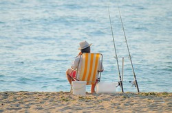 back of alone fisherman sitting in a beach chair with hat by the sea and fishing