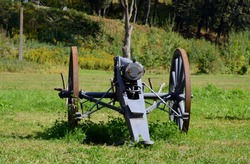 Back of an old, grey, metal WWI cannon replica with big rusty wheels, metal base, compartment for missiles and barrel standing in the middle of a grass and shrub covered field seen in summer in Poland
