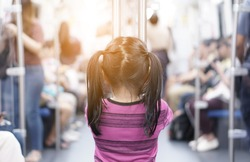 back of asian child or kid girl enjoy standing in bogey of sky train or electric train with underground railways or subway metro and holding rail for happy fun travel in city street on warm light