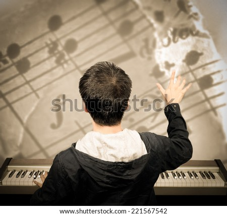 back of asian male musician / pianist / composer arranges music note on imagination