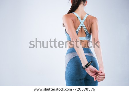 Back of beautiful fitness woman. Fitness girl do sport exercises isolated over gray background #720598396