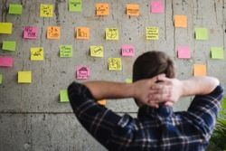 Back of entrepreneur sitting in office and look at colorful sticky message on cement wall. Work lifestyle concept.  Selective focus.